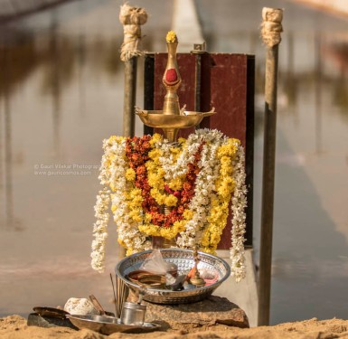 A garlanded lamp is set up for the pooja